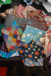 My messy craft table. There are some awesome fabrics waiting to be turned into bandanas in that pile!