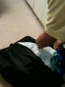 My husband zipping the car seat bag, with my diapers stowing away inside